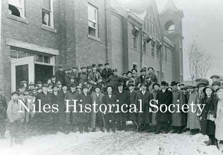 A large group of Niles citizens standing outside the fire station on Franklin Alley on a cold wintry day.