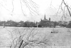 The Mahoning River in full spate from the south side of Niles looking north toward St. Stephen's Church & school. 1913 flood.