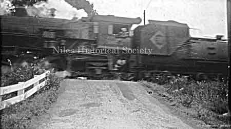 Steam locomotive and tender of the Erie Rail Road as it crosses over County Line Road in Mineral Ridge.