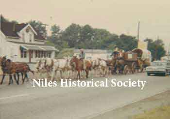 Parade of conestoga wagons on the move in front of the Carlisle home and the restaurant eatery across Niles-Vienna Road.