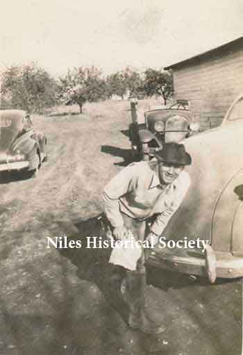 Phyllis' dad cleaning his boots after working in the barn. In the background is the Blott apple orchard which provided fruit for sale at the market. The car beside him is a 1941 Plymouth and older cars behind him are not identified.