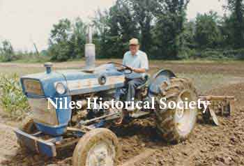 Phyllis' dad on tractor, 'Big Blue', after retirement from the farm market.