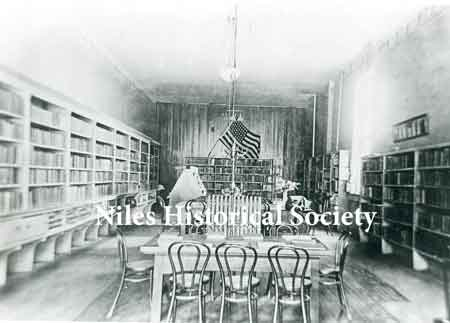 The interior of the Niles Library when it was in a rent free room owned by W. A. Thomas on the bend of Furnace Street (East State Street). It contained a total of 2,882 books and operated during the hours of 9-5, 6:30-8:30 daily.