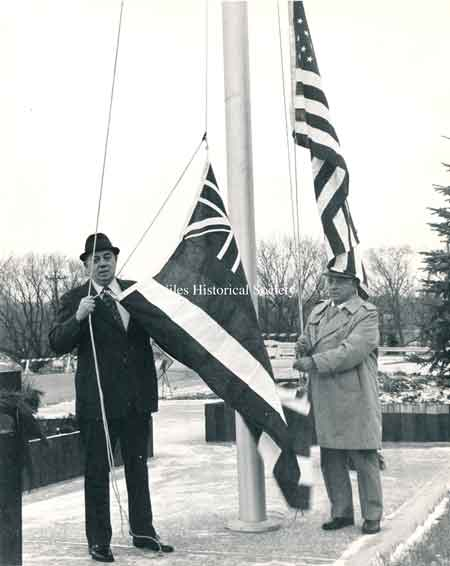 John Scott and Police Chief Ross raising the flag at the new Safety-Services Complex on East State Street.