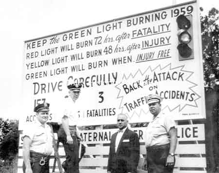 Injury Light located at the side of Robbins and Vienna Avenues. Pictured are John 'Burgaundy' Marsico, Glen Smith, Police Chief Ross and John Scott. Photo 1959
