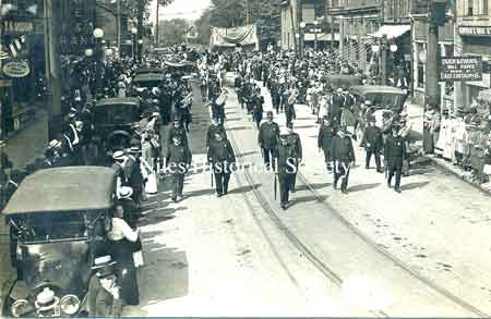 "The ""Blue Knights"" of the Niles Police force, as shown here, were always at the head of many parades that were organized for every public occasion. Leading a parade down East State Street toward the curve from South Main Street.Picture circa 1915."