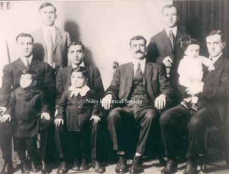 Isaac Shaker's brother Joseph holding toddler Mitchell Shaker, Isaac Shaker's father Shaker Aoud, Isaac Shaker with young son Simon Shaker in front, Isaac Shaker's brother Samuel with unknown toddler in front. Back row left Fred Joseph and Isaac's brother and partner in the store Akel Shaker.